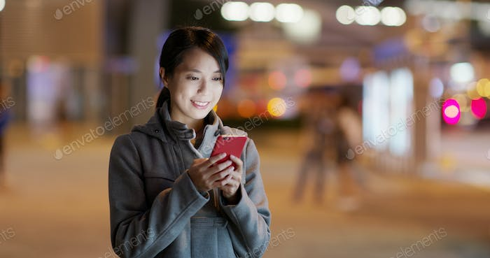 Woman look at the cellphone and searching for location in the the street at night