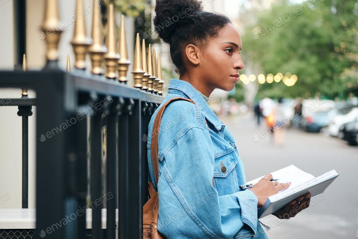 African American student girl in denim jacket with notepad thoughtfully studying on city street