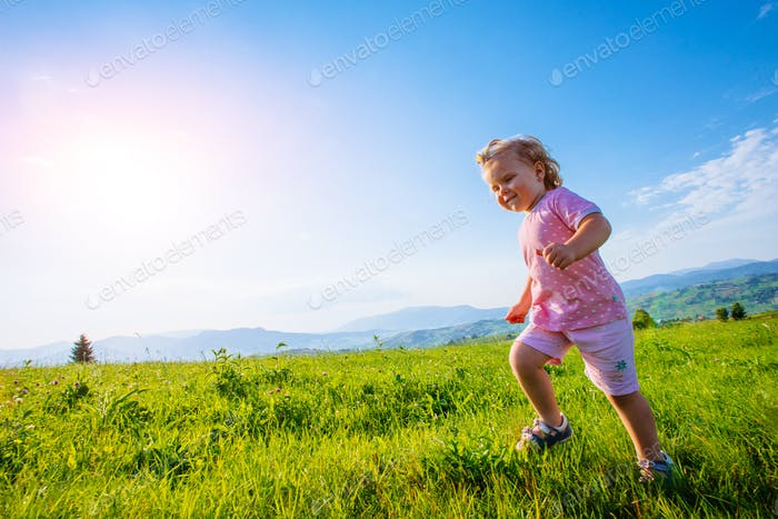 Little toddler girl running in a beautiful field