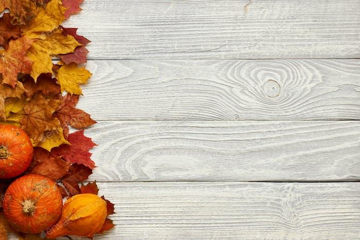 Herbstblätter und Kürbisse über alten Holzhintergrund