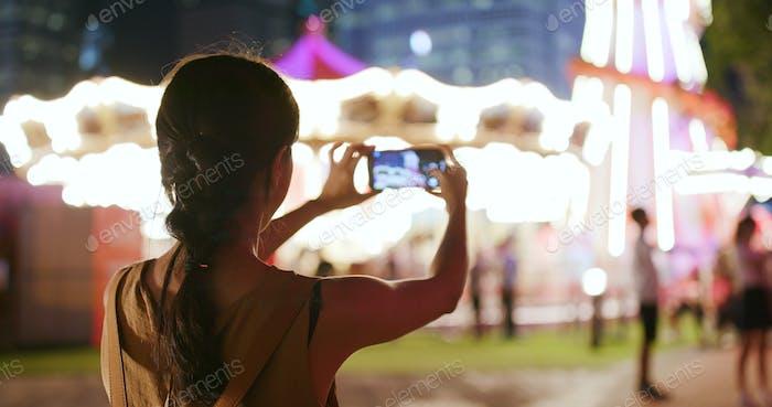 Frau nimmt Foto und Video im Vergnügungspark in der Nacht