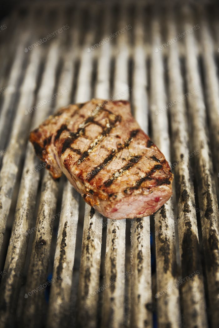 Close up high angle view of a steak on a griddle.