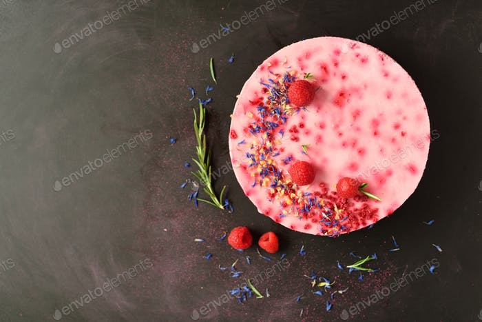 Delicious raspberry cake with fresh berries, rosemary and dry flowers on dark vintage background