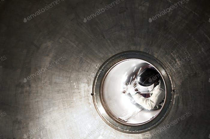 Welder or metal worker working inside a tunnel