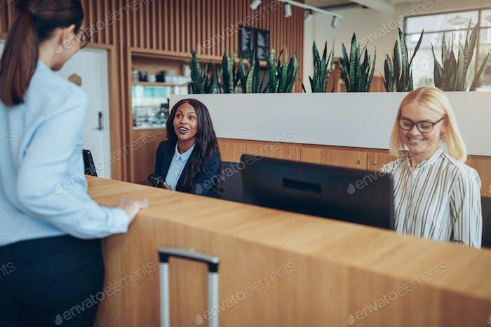 Lächelnder African American Hotel-Concierge hilft ein Gast Check-in