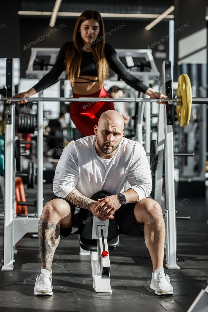 Brutal athletic man sits on the sport bench and slender girl stands behind him next to the sport