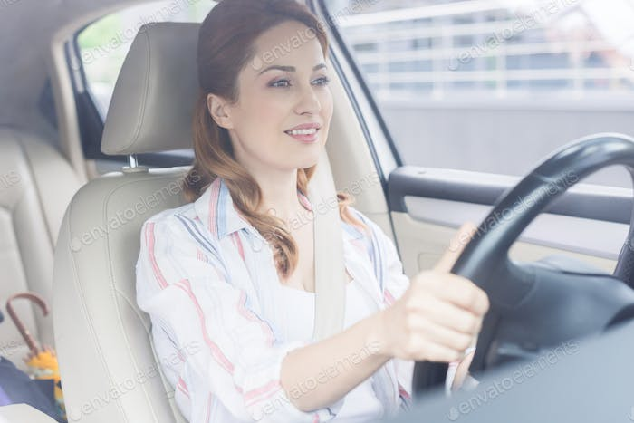 portrait of smiling woman with hands on steering wheel driving car