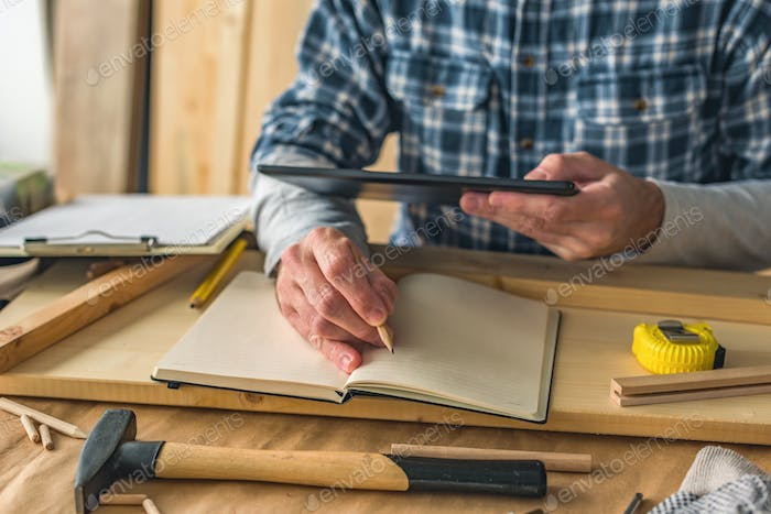 Carpenter using digital tablet to complete project to do list