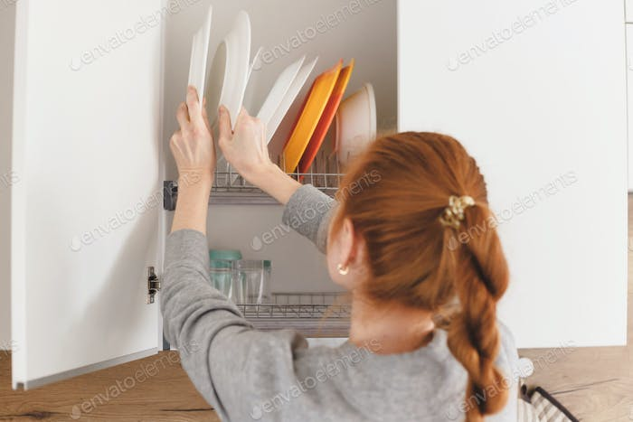 Opening kitchen cabinet door, woman putting plates into it.