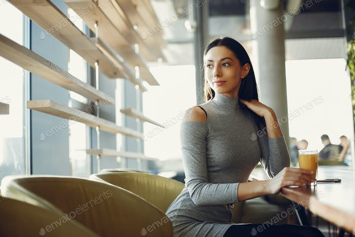 Fashion young girl sitting in a cafe