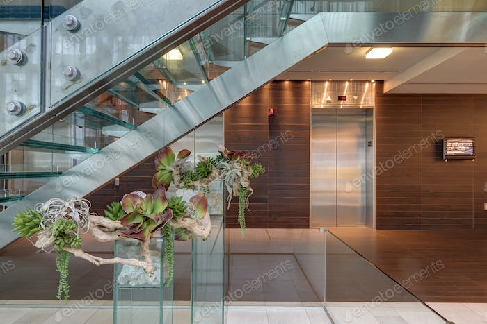 Glass staircase and elevators in hotel lobby