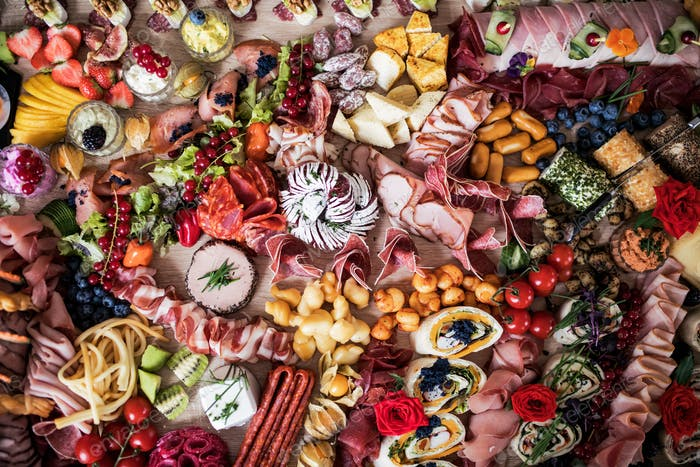 A top view of various food and snacks on a tray on a indoor party, a cold buffet.