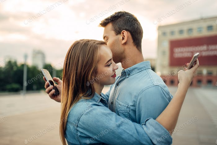 Couple hugs and using gadgets, modern relationship