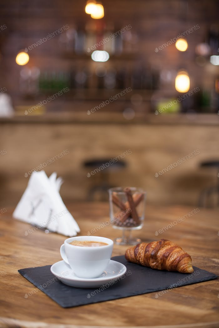 Hot coffee and croissant on coffee shop wooden table