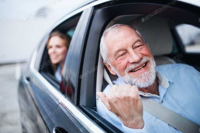 Senior man and young woman sitting in car, looking out of window