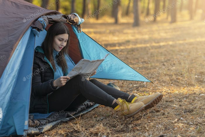Young woman checking map in camping tent