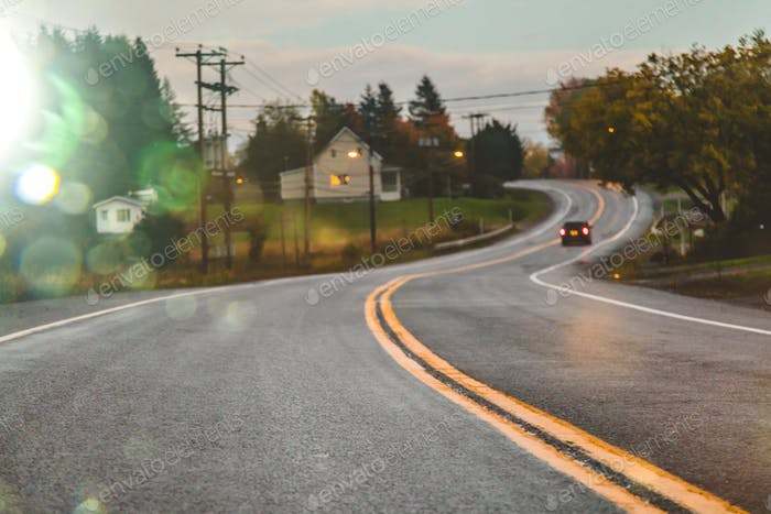 Car driving on road in evening