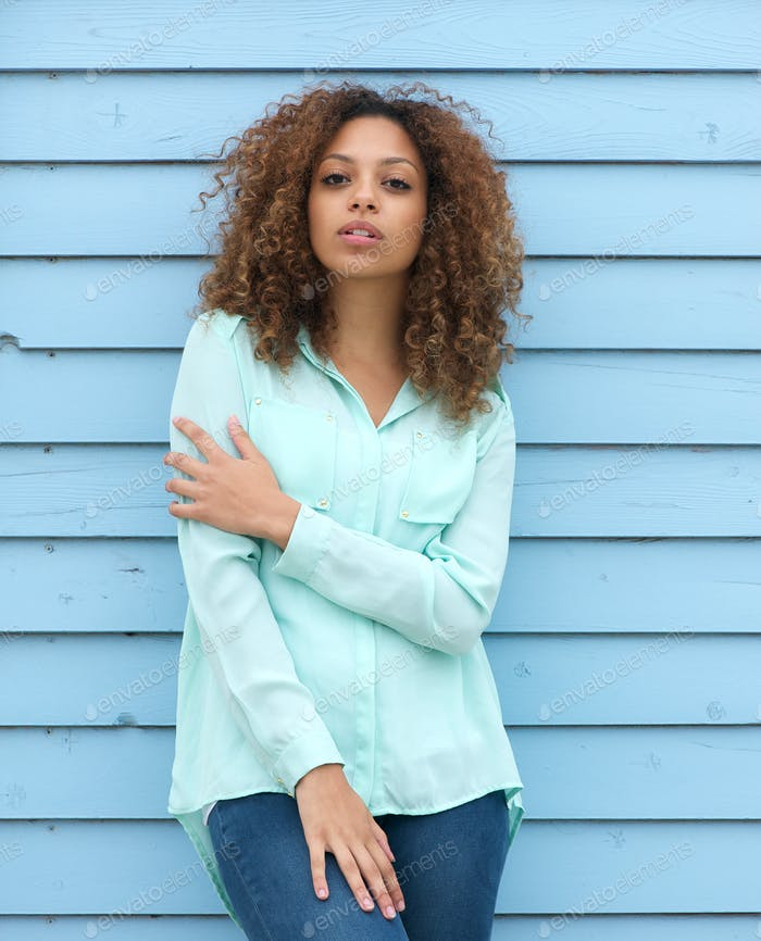 Female fashion model with curly hair standing outdoors