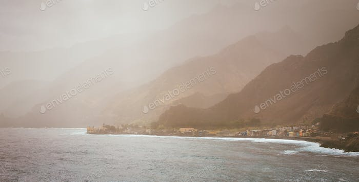 Bluff volcanic coastline covered by sunlight penetrates dust. Silhouette of mountain ridges. Road to
