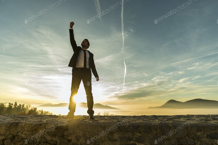 Triumphant businessman greeting a new day