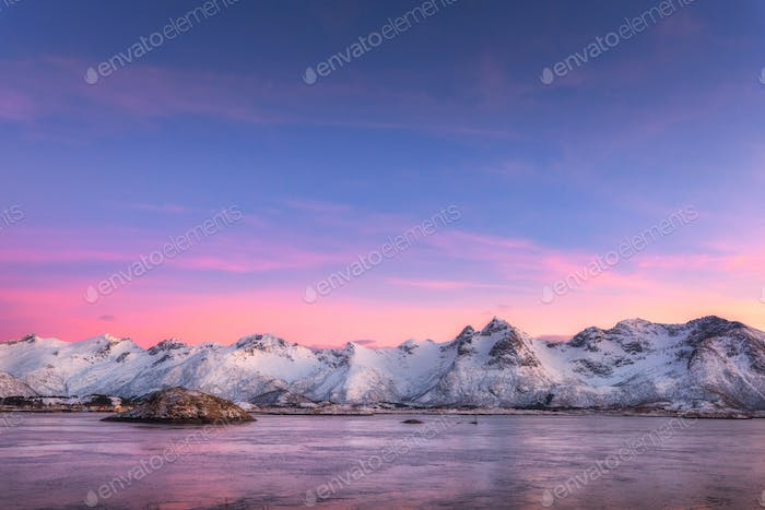 Snow covered mountains and colorful sky reflected in water