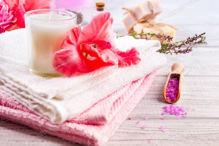 Spa set with flower, candle, bath soap and massage salt on wooden background