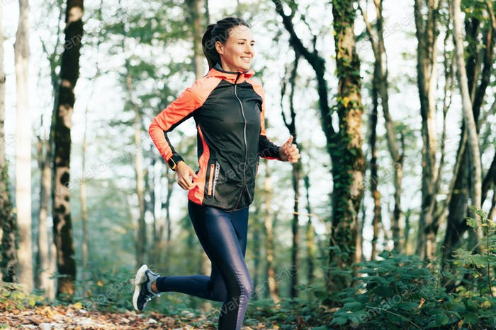 Portrait of a runner woman in a forest. Healthy lifestyle concept.