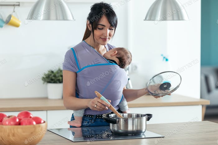 Pretty young mother with little baby in sling cooking in the kitchen at home.