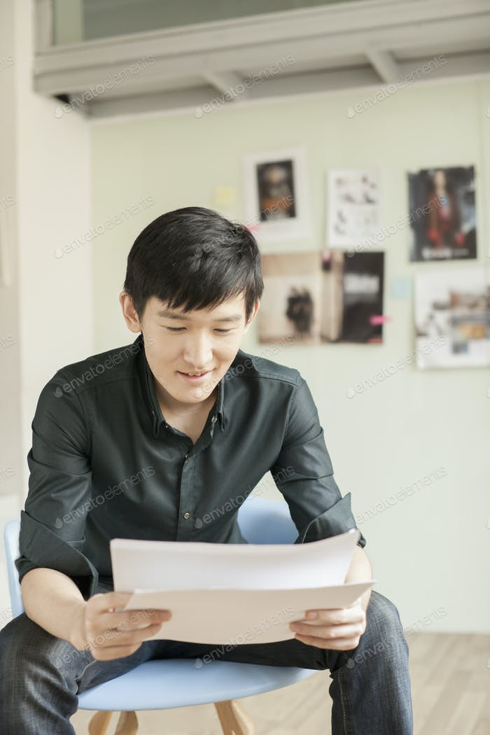Professional Man Looking at Papers in Office