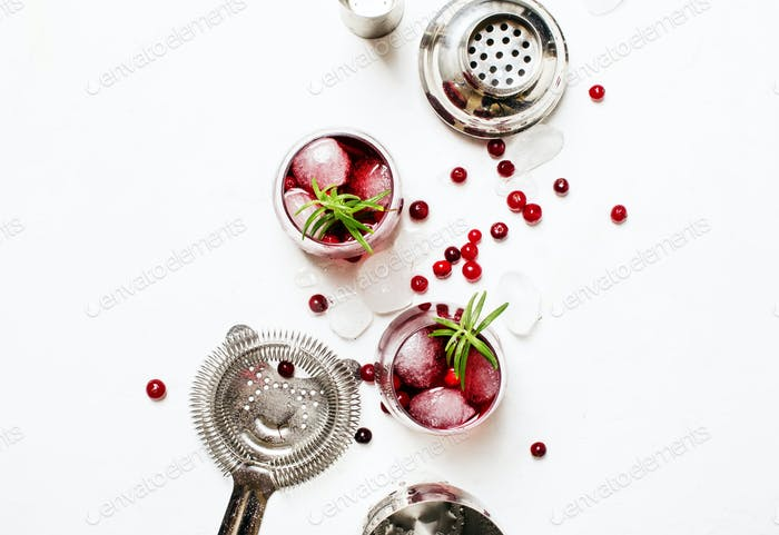 Cranberry cocktail with ice, rosemary and berries, bar tools