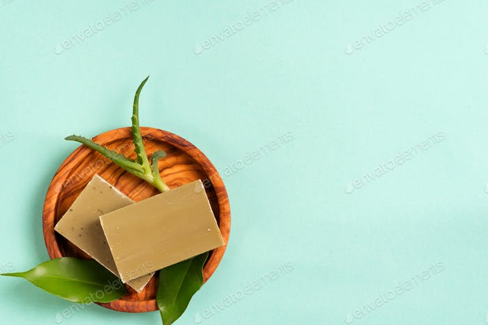 Bars of green natural olive oil soaps with green leaves and aloe vera in a plate on blue background