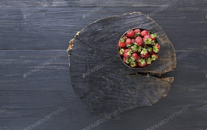 Red fresh strawberries on black rustic wood background