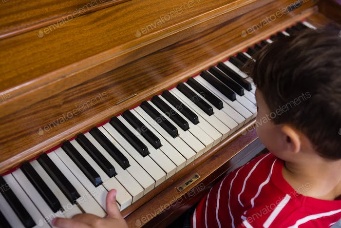 High angle view of boy playing piano in classroom