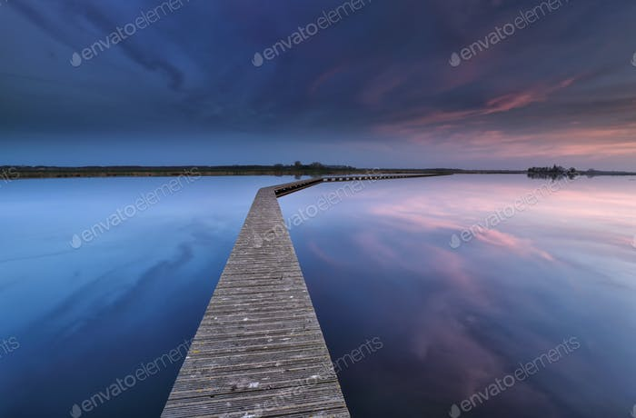 wooden walkpath on water at dawn