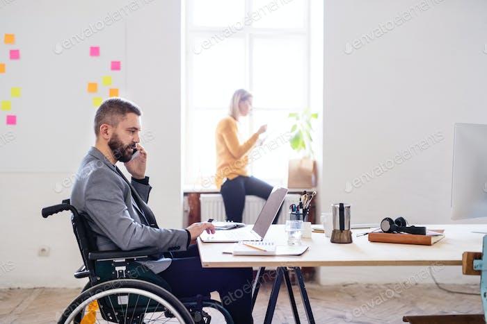 Zwei Geschäftsleute mit Rollstuhl im Büro.