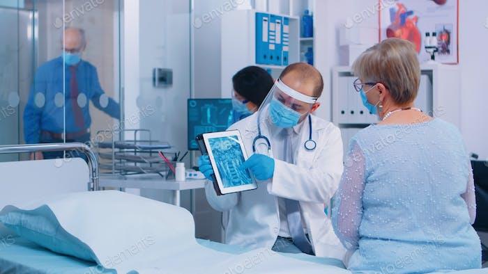Arzt zeigt pensionierte Frau Radiologie Scan auf Digital-Tablet