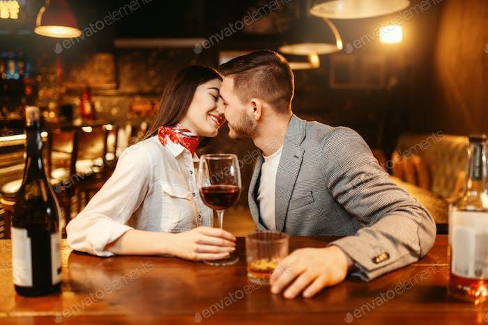 Noche romántica en el bar, pareja besándose en el mostrador