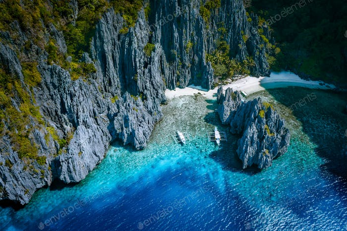 El Nido, Palawan, Philippines. Aerial above view of Secret hidden rocky lagoon beach with tourist