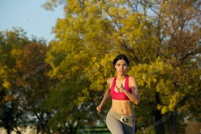 Attractive young woman running outdoors in the park