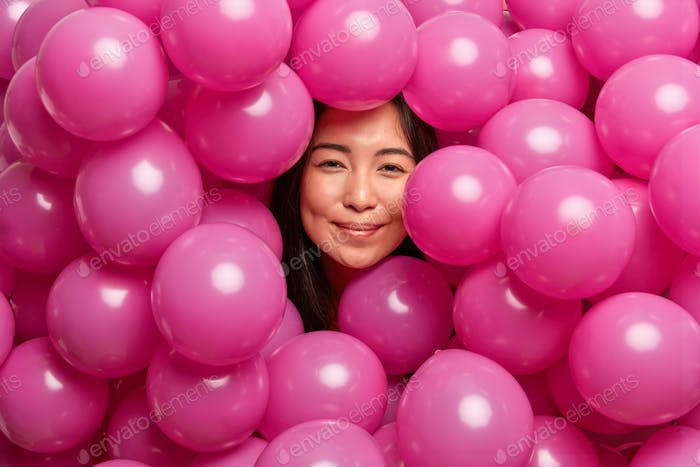 Pleased young brunette Asian woman being happy at birthday party surrounded with pink inflated ballo