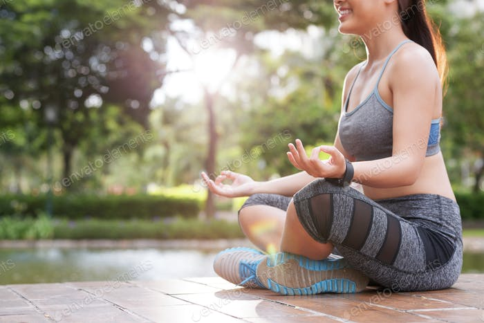 Cheerful sportive woman meditating in sunlight