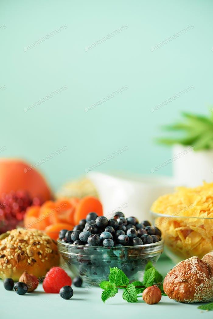 Deliciosos ingredientes para el desayuno. Copos de maíz, nueces, frutas, bayas, leche, yogur, naranja, plátano