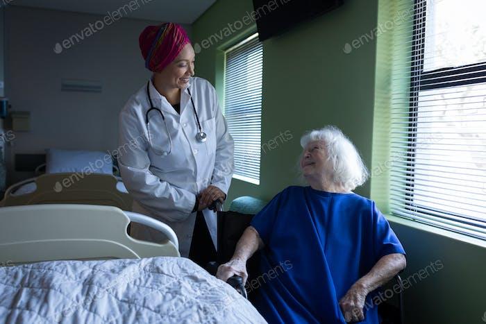 Vorderansicht einer gemischten Rasse Ärztin im Gespräch mit einem älteren kaukasischen Patienten im Krankenhauszimmer
