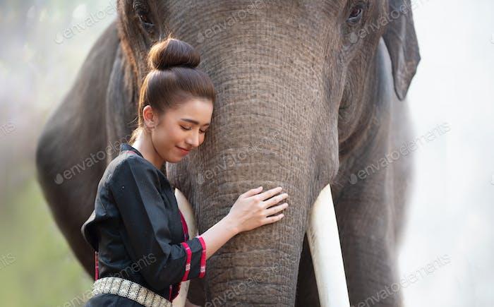 Asian women standing by elephant