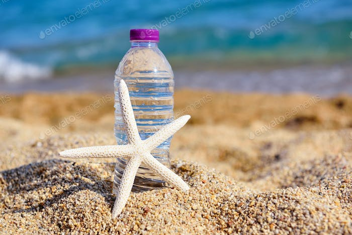 The white starfish and the bottle water on a hot day at the beac