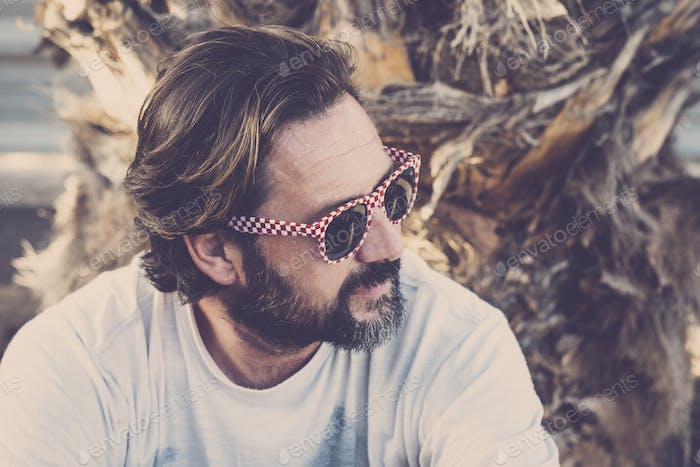 Handsome adult caucasian man portrait in outdoor with alternative sunglasses and beard