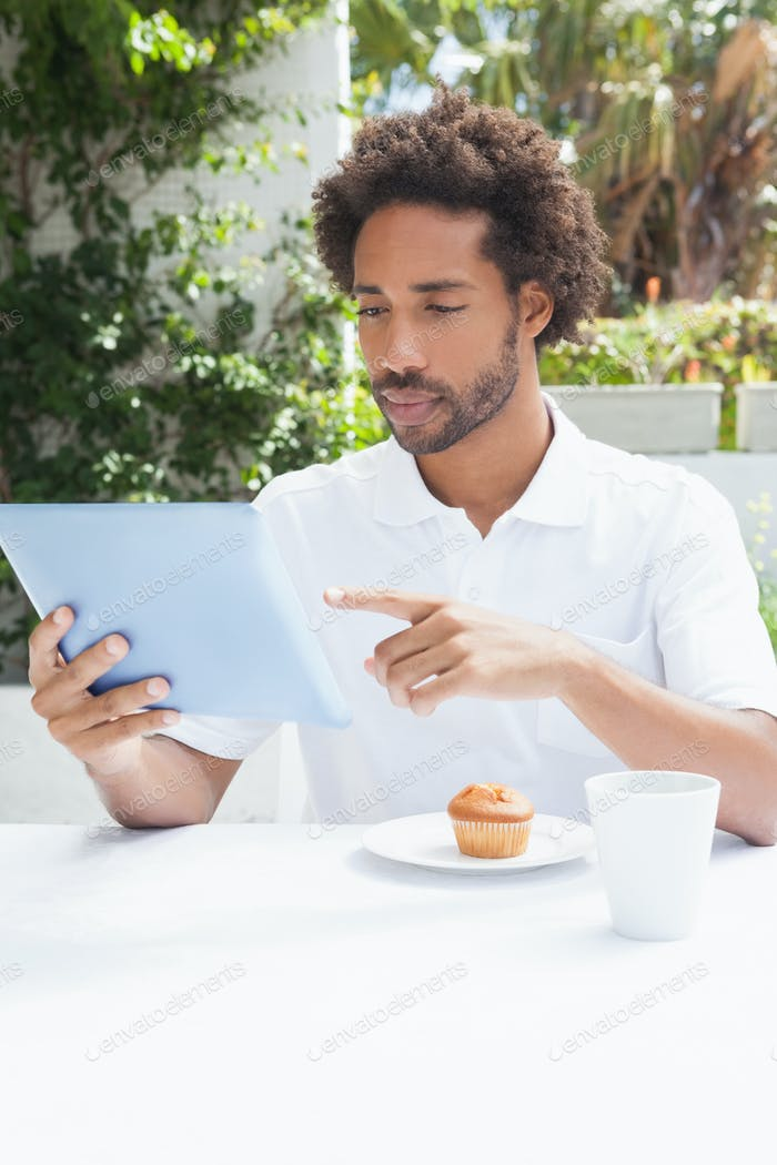 Thoughtful man having a coffee using tablet outside at the coffee shop