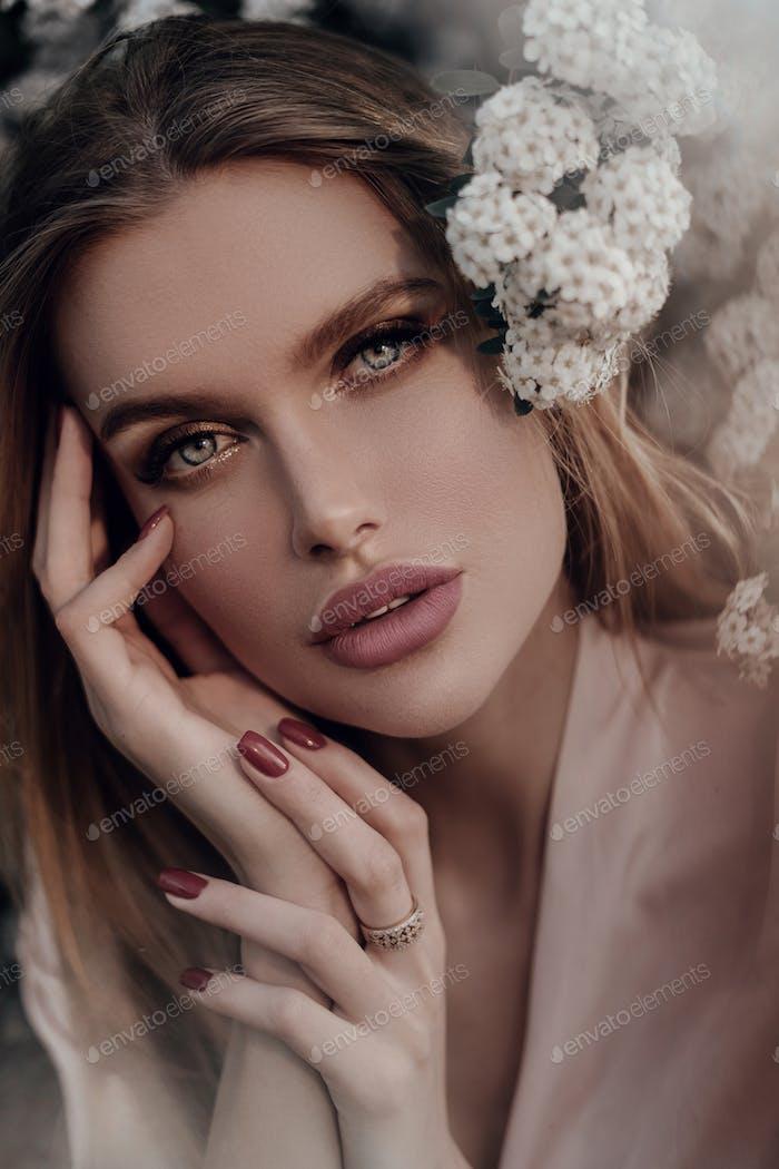 Portrait of a beautiful blonde girl in flowers