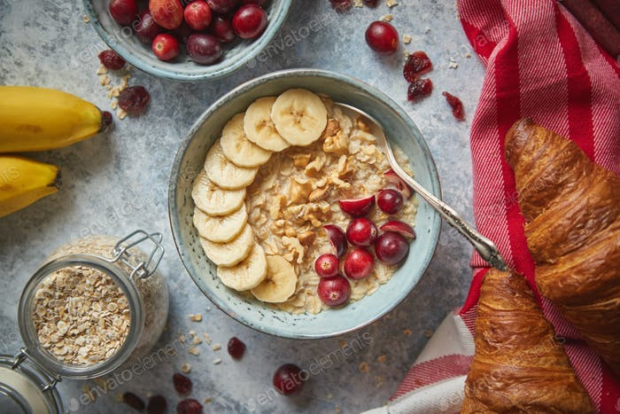 Ceramic bowl of oatmeal porridge with banana, fresh cranberries and walnuts