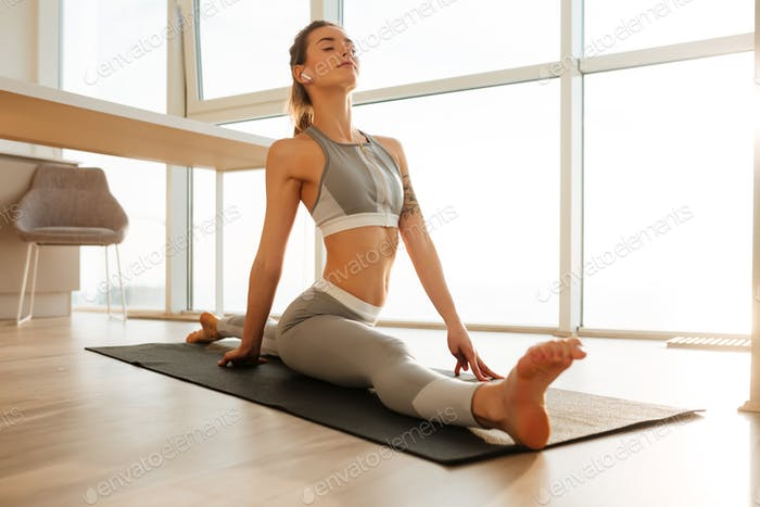 Pretty lady in sporty top and leggings practicing fitness on yoga mat listening music at home